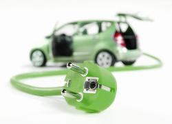 Grünes Auto im Hintergrund mit Stecldose zum Laden