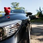 Rotes Sparschwein platziert auf der Motorhaube eines Luxusautos