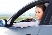 Junge Frau lächelt aus Autofenster