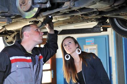 Mechaniker und junge Frau begutachten Auto von unten