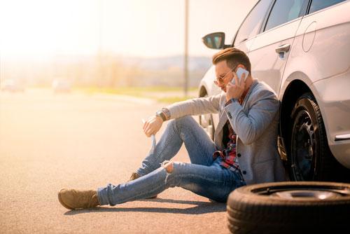 Junger Mann sitzt mit Radschlüssel neben seinem Auto und telefoniert