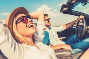 Junges Paar genießt die Fahrt in einem offenen Cabrio bei Sonnenschein